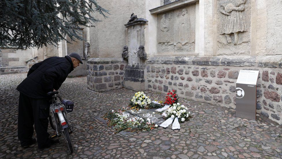 A man with a bicycle looks at a memorial plaque against anti-Semitism outside the Stadtkirche in Wittenberg, Germany (4 February 2020)
