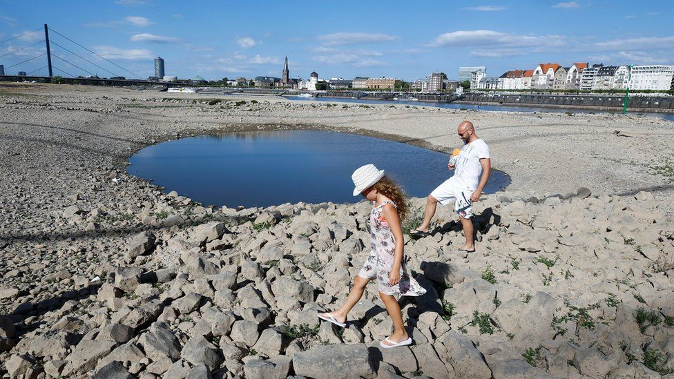 A family walks next to a puddle in the partially dried riverbed of Rhine, in front of the skyline of Dusseldorf, Germany, July 31, 2018