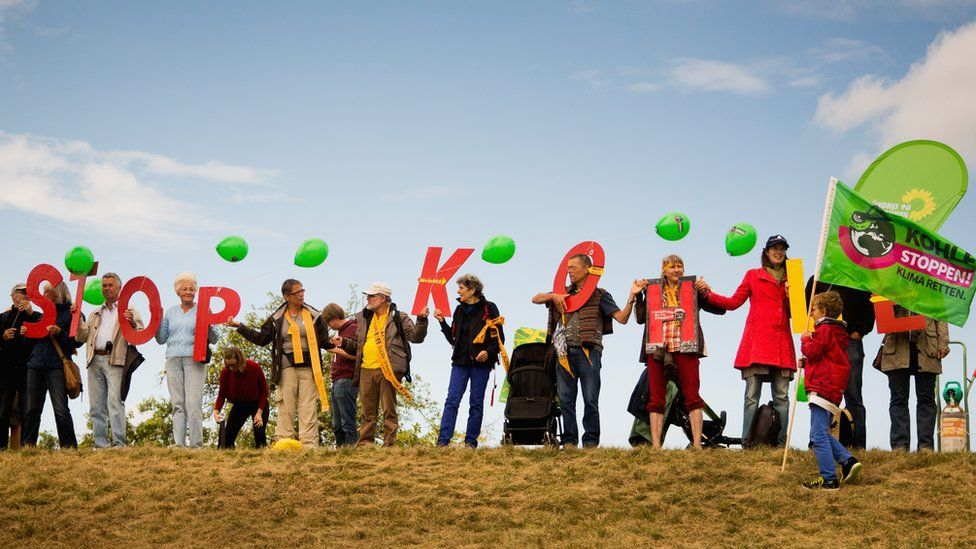 """Activists hold letters """"Stop Kohle"""" (Stop Coal) against expansion of open-cast coal mine near Gross Gastrose, Germany. 23 August 2014"""
