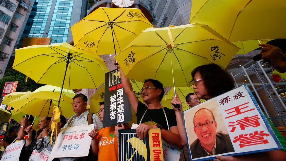 In this July 23, 2015 file photo protesters holding yellow umbrellas and a picture of human rights activist Wang Qingying, protest to demand Wang's release, in Hong Kong