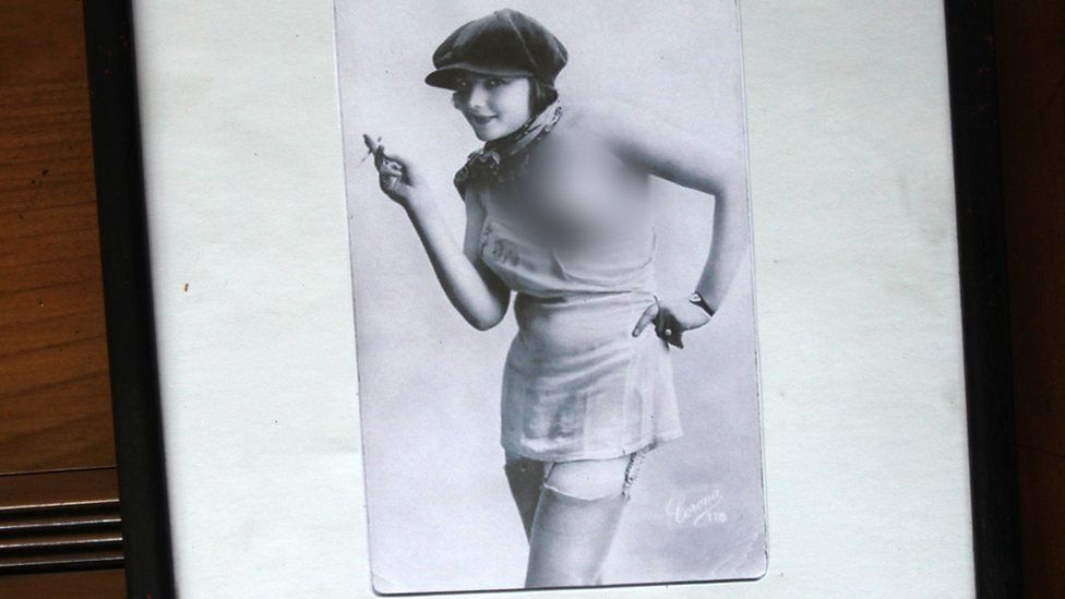 Another picture, a woman wearing a cap pulls down her dress to expose her breast