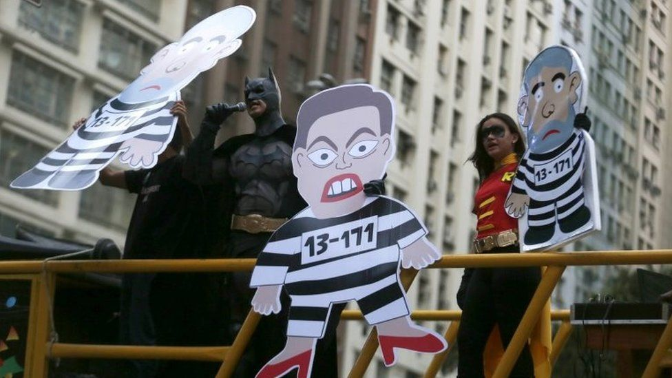 A demonstrator dressed as Batman speaks next to cardboard cut-outs depicting Dilma Rousseff and former President Luiz Inacio Lula da Silva during a protest in Rio de Janeiro on 3 September, 2015
