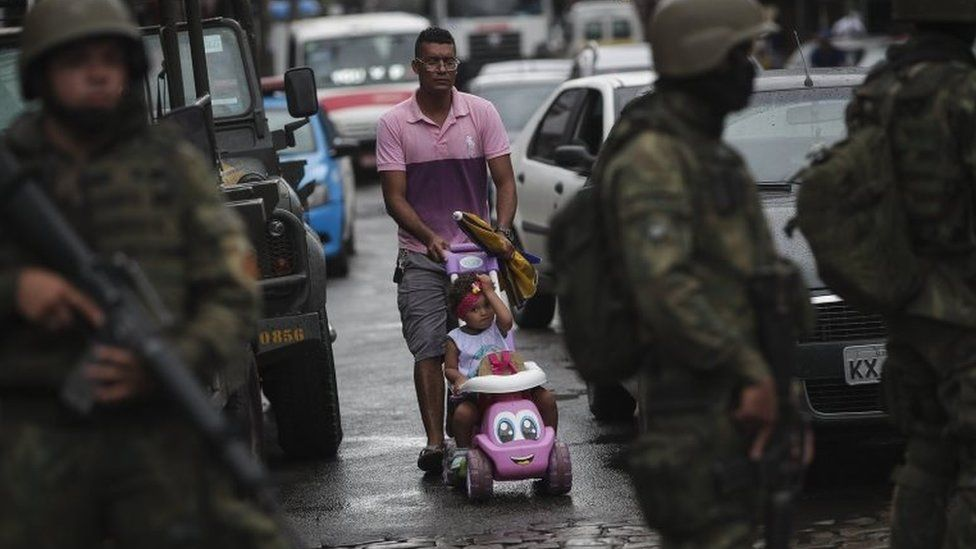 A man passes by a group of soldiers that participate in a security operation in Rio de Janeiro, Brazil, 23 February 2018