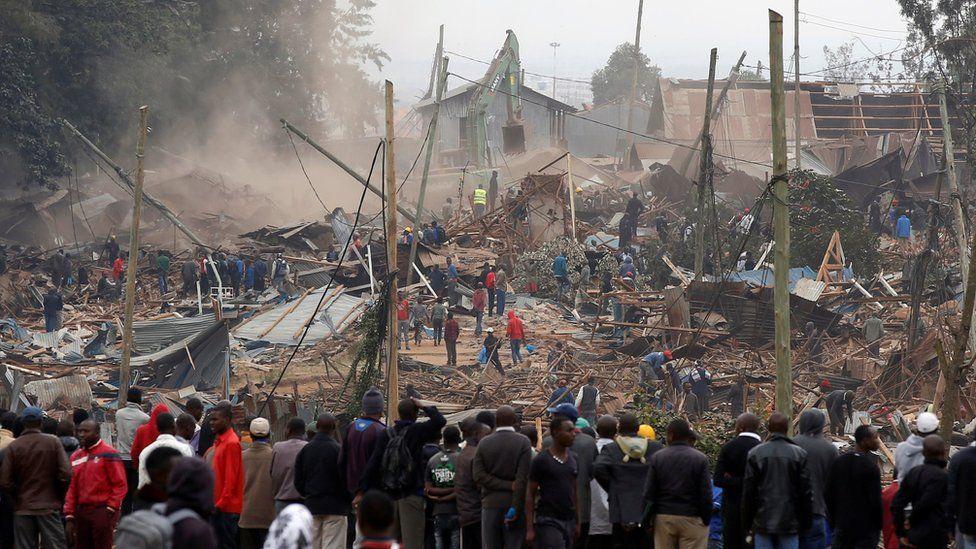 Onlookers watch as bulldozers demolish houses to make way for a new road in the Kibera slum in Nairobi, Kenya, July 23, 2018.
