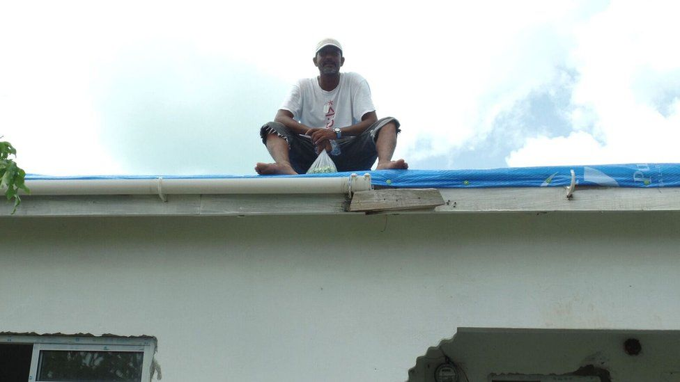 Devon Warner replaces the missing roof on a relative's home with tarpaulin.