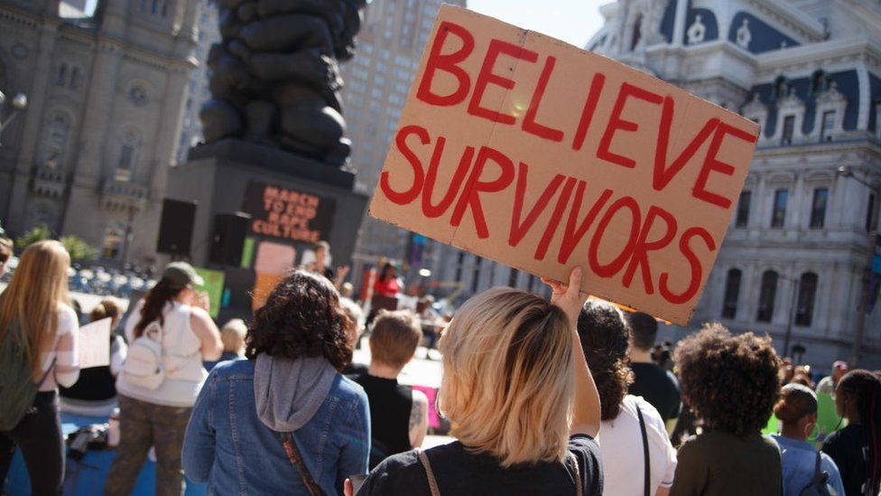 """A woman holds a """"Believe Survivors"""" sign at a rally"""
