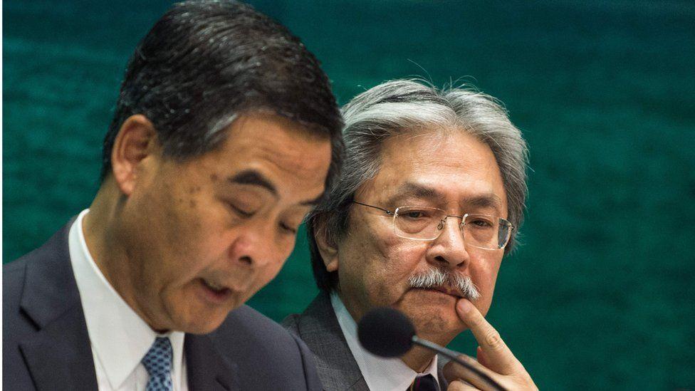 "This file photo taken on September 21, 2016 shows Hong Kong's Financial Secretary John Tsang Chun-wah (R) gesturing as Hong Kong""s Chief Executive Leung Chun-ying writes notes during a press conference in the Central Government office in Hong Kong."