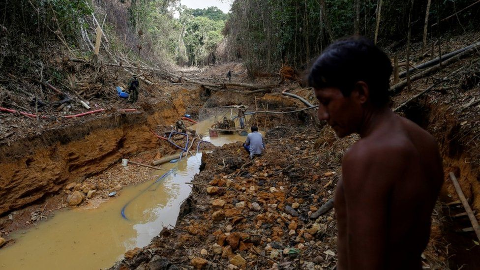 A Yanomami indian follows agents of Brazil's environmental agency in a gold mine during an operation against illegal gold mining on indigenous land, in the heart of the Amazon rainforest, in Roraima state, Brazil April 17, 2016
