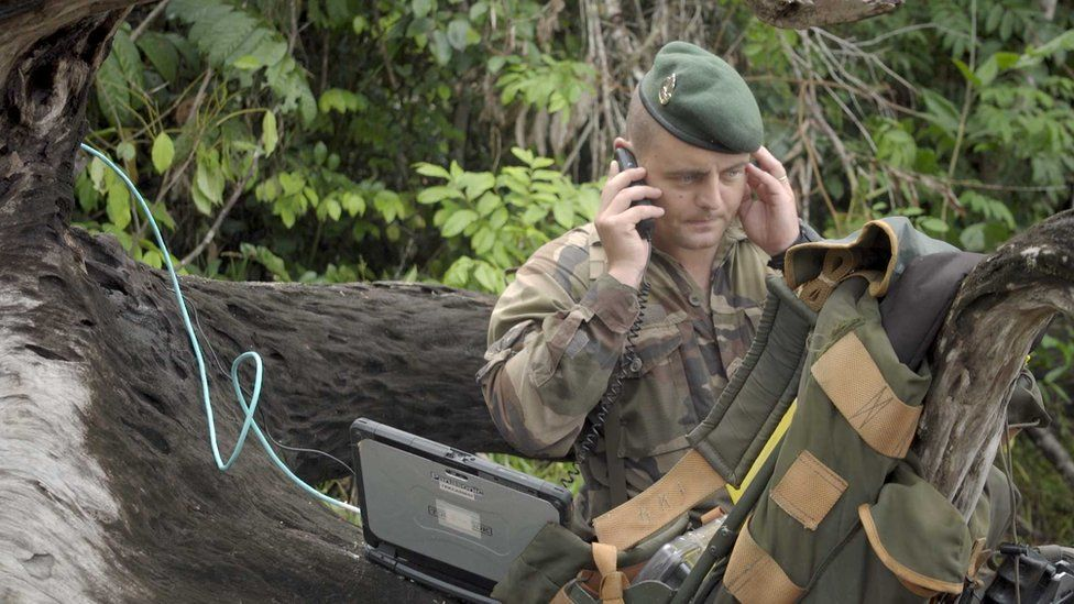 Captain Vianney uses a satellite phone to coordinate the operation from within the jungle
