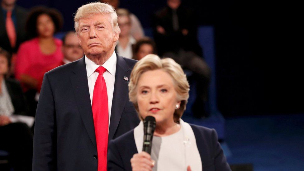 Republican US presidential nominee Donald Trump listens as Democratic nominee Hillary Clinton answers a question from the audience during their presidential town hall debate in Missouri on 9 October