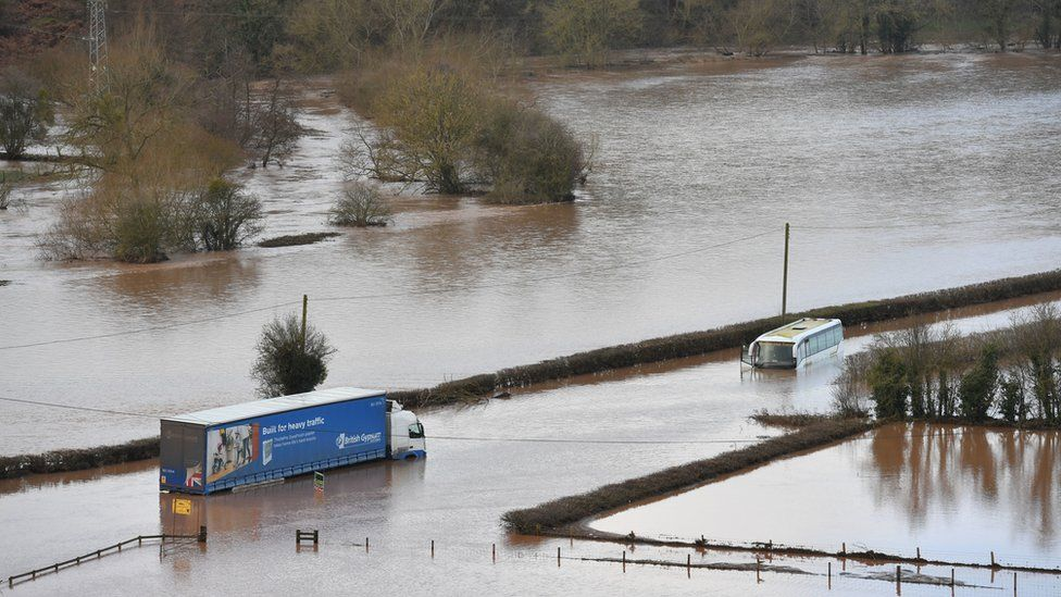 A lorry and a coach submerged in floodwater from the River Teme on the A443 near Lindridge, Worcestershire, as the aftermath of Storm Dennis brings heavy rain and flooding