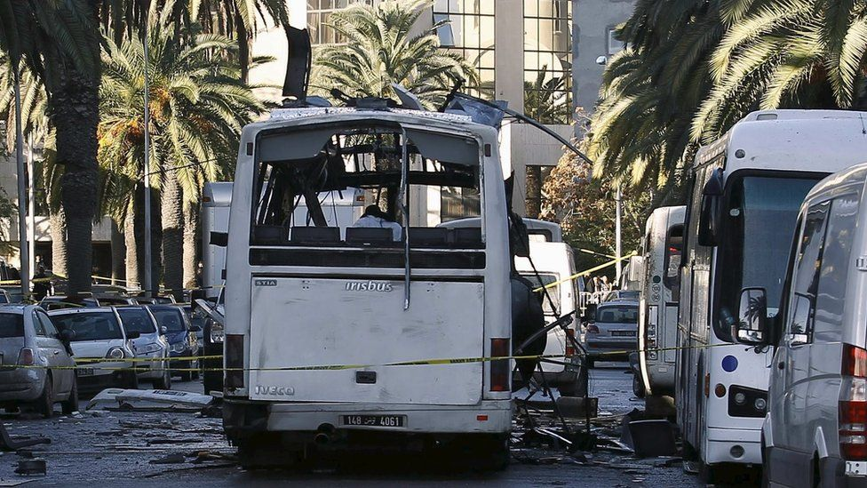 A damaged bus is seen at the scene of a bomb attack in Tunis