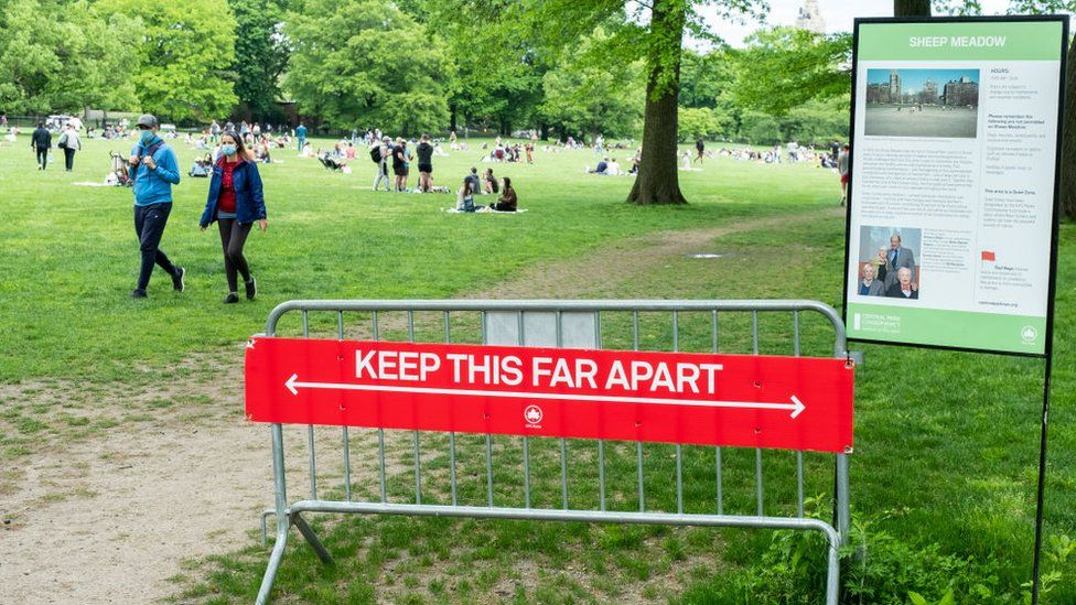 """On Memorial Day weekend a sign at the entrance of Sheep Meadow in Central Park says """"Keep this Far Apart"""" physically showing how far 6 feet is with crowds of people in side the park"""