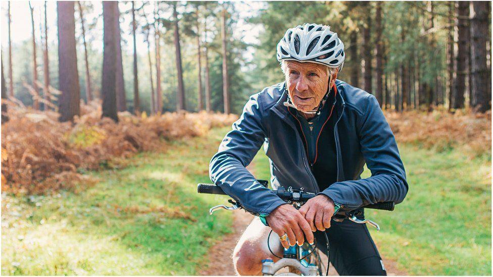 Pensioner on bike in forest