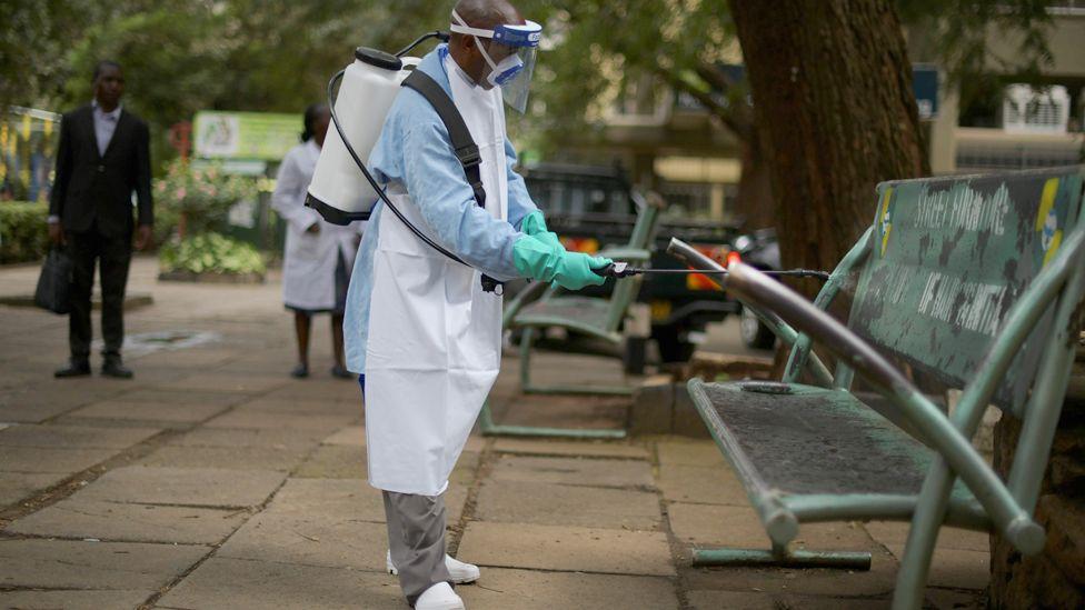 A man spraying a bench with a chlorine solution in Nairobi, Kenya -
