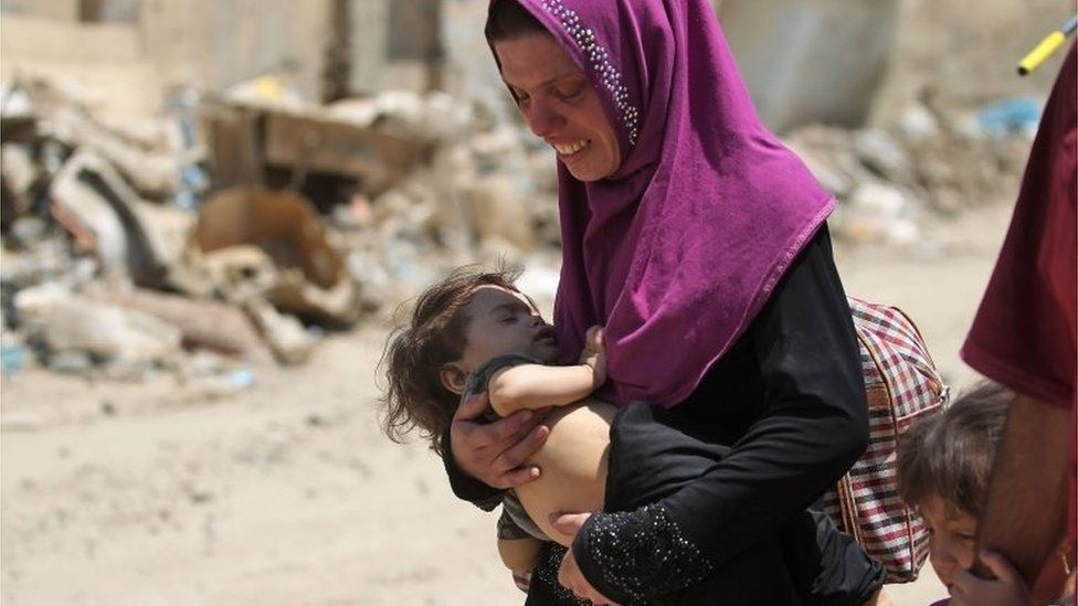 An Iraqi woman carries a child as she flees from the Old City of Mosul on June 20, 2017, during the ongoing offensive by Iraqi forces to retake the last district still held by the Islamic State (IS) group.