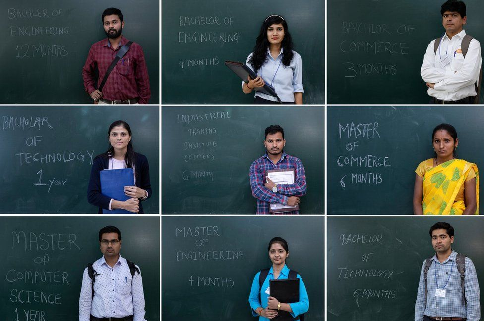 Unemployed Indians pose in front of a blackboard with their qualifications