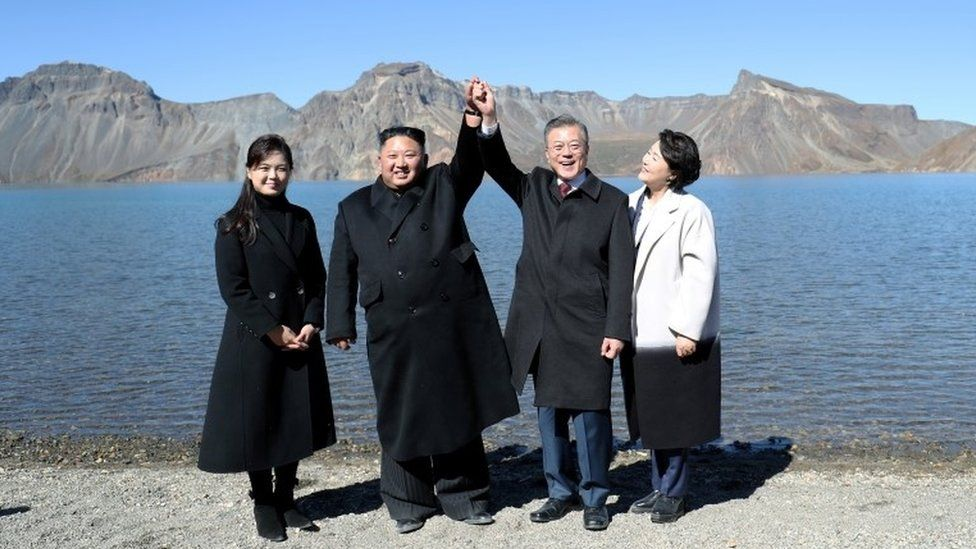 Kim Jong-un and Moon Jae-in hold hands on Mt Paektu in North Korea, with their wives next to them