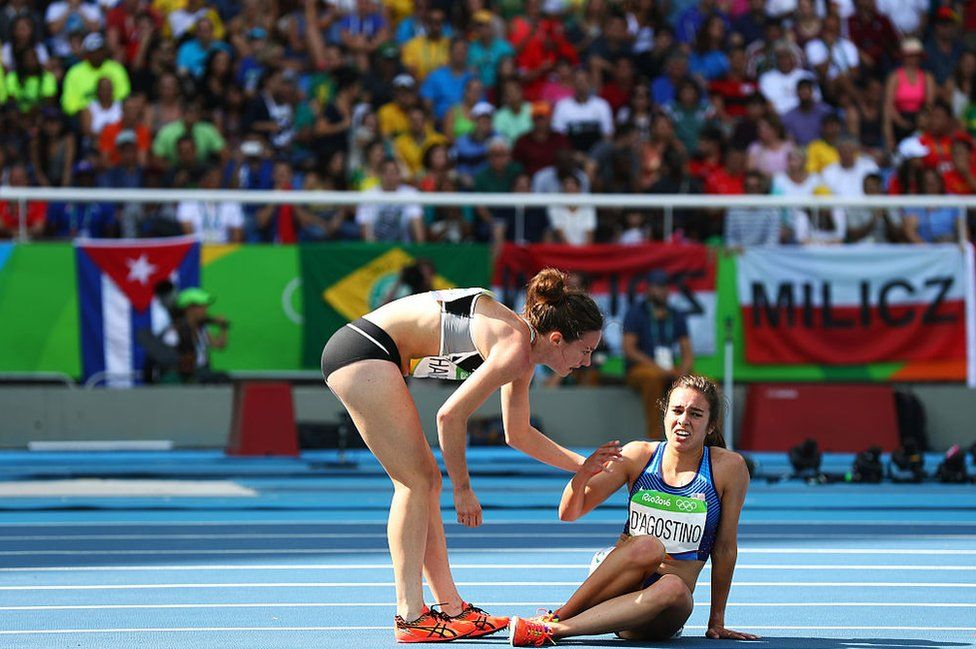 Abbey D'Agostino of the United States (R) is assisted by Nikki Hamblin of New Zealand after a collision during the Women's 5,000m Round 1 - Heat 2 on Day 11 of the Rio 2016 Olympic Games at the Olympic Stadium on 16 August 2016 in Rio de Janeiro, Brazil.