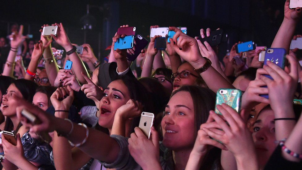 A concert with people holding smartphones aloft