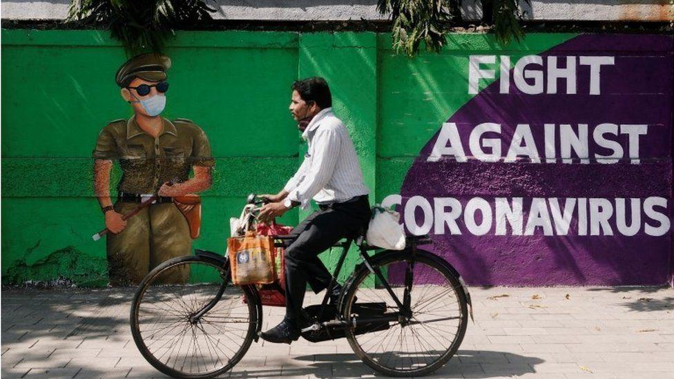 A man cycles past a graffiti covered wall amidst the spread of the coronavirus disease (COVID-19) on a street in Navi Mumbai, India January 21, 2021.