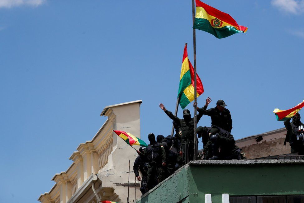 Police officers flying flags on the roof of a police station in La Paz on Saturday