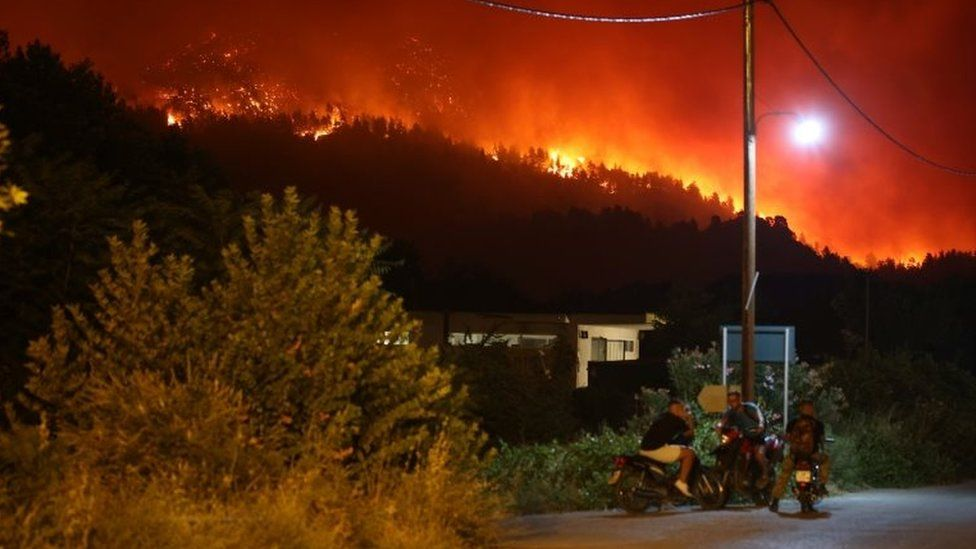 People gather on motorbikes as wildfire flames rise behind them on Evia