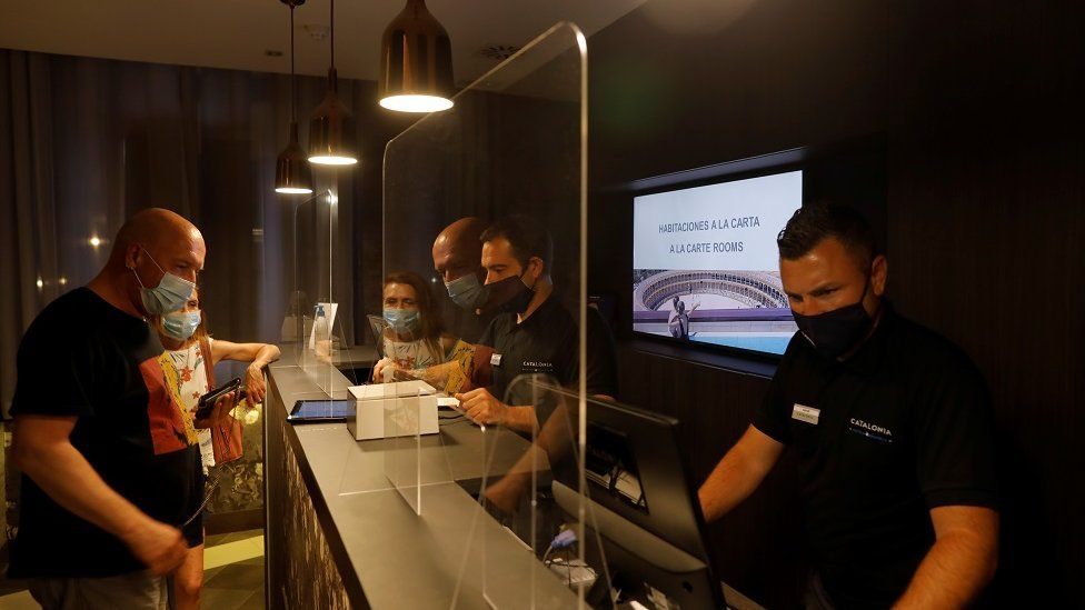 German tourists are attended by receptionists, wearing protective face mask as they do the check-in at the Catalonia Ronda hotel, in southern Spain