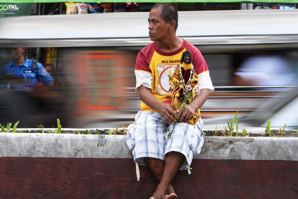 A man holds a replica of the Black Nazarene in Manila (7 Jan 2019)