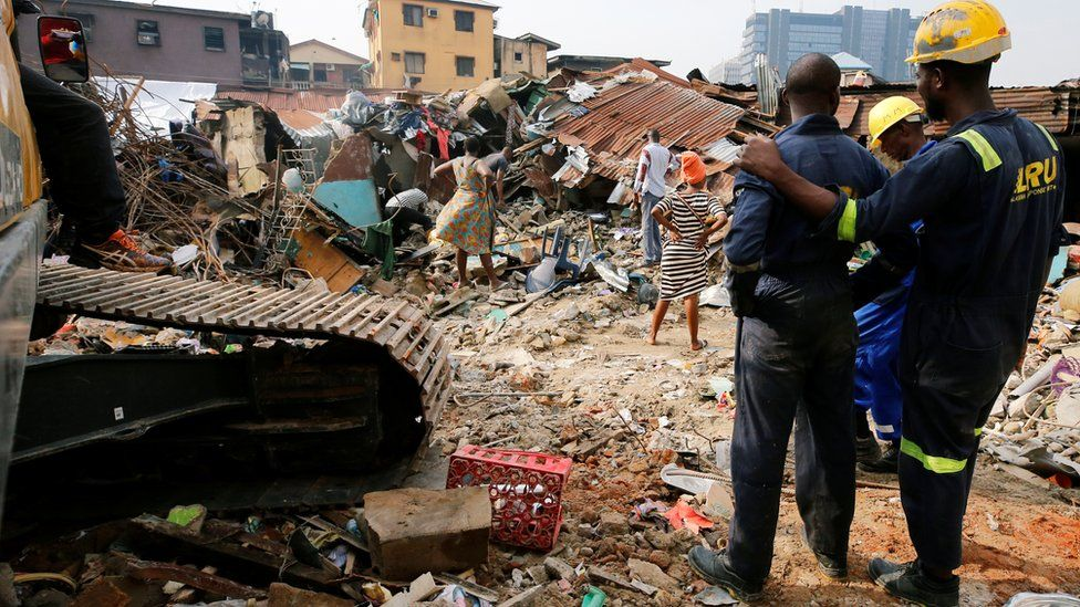 People looking on at a building that collapsed on Lagos island March 2019