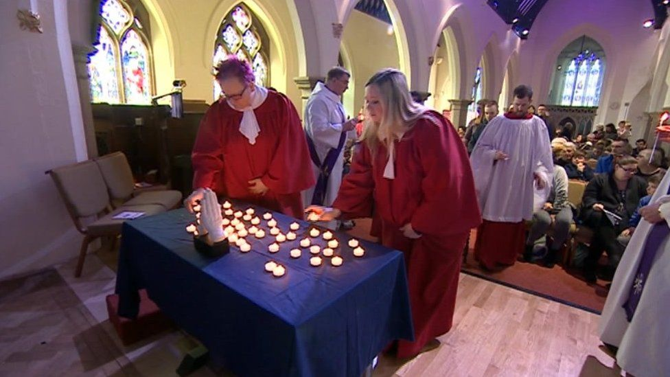 People lighting candles during the service