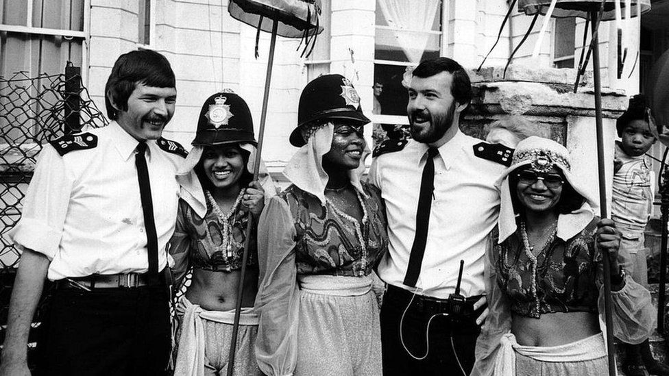 Police officers with Notting Hill Carnival performers in 1980