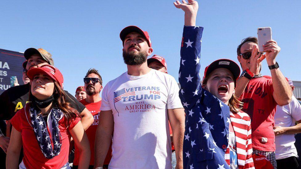 "A girl raises a hand as she reacts during U.S. President Donald Trump""s campaign rally at Laughlin/Bullhead International Airport in Bullhead City, Arizona, U.S., October 28, 2020"