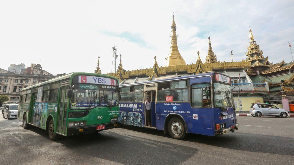 Two bus driving together on the Sule pagoda cycle road ( land mark of central Yangon), to the bus stop on 18 January 2017 afternoon