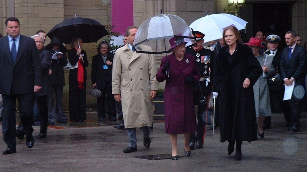 The Queen in Manchester under an umbrealla