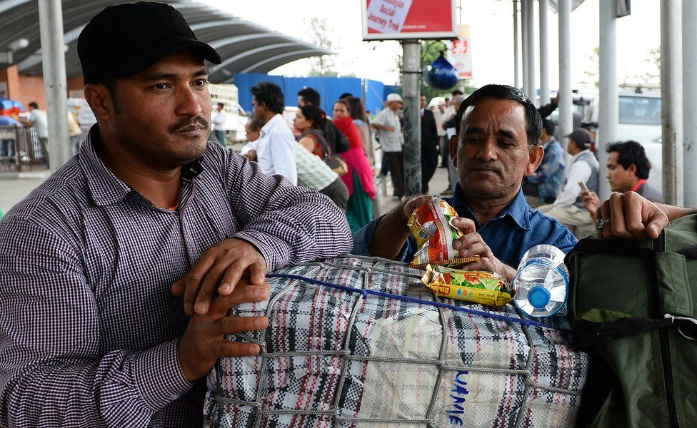 Nepalese migrant workers stand with their luggage at Tribhuvan International Airport in Kathmandu, after returning from The United Arab Emirates.