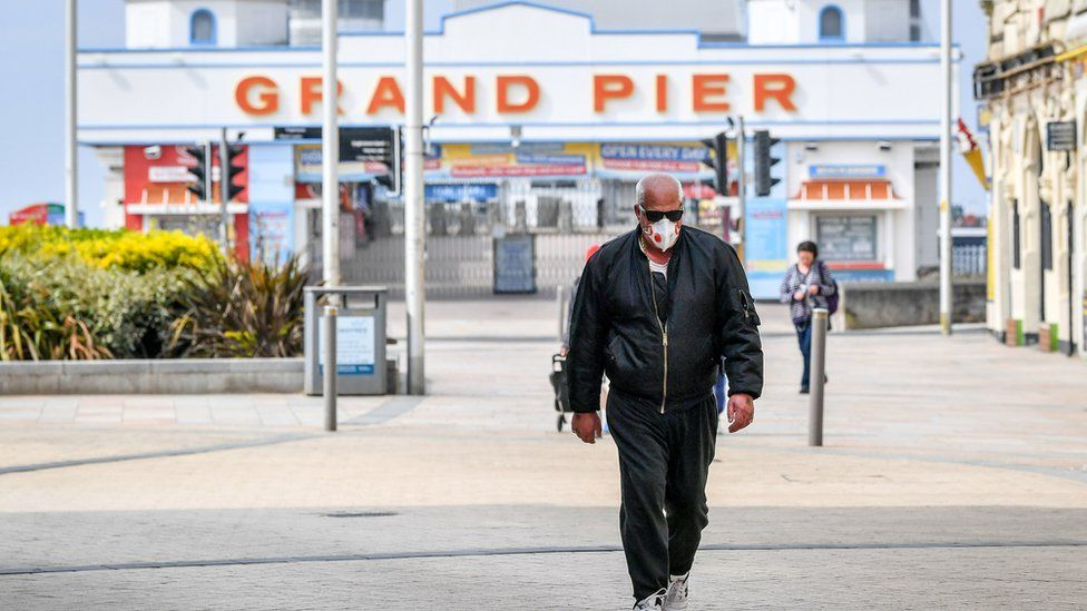 Man walks in front of Grand Pier at Weston-super-Mare