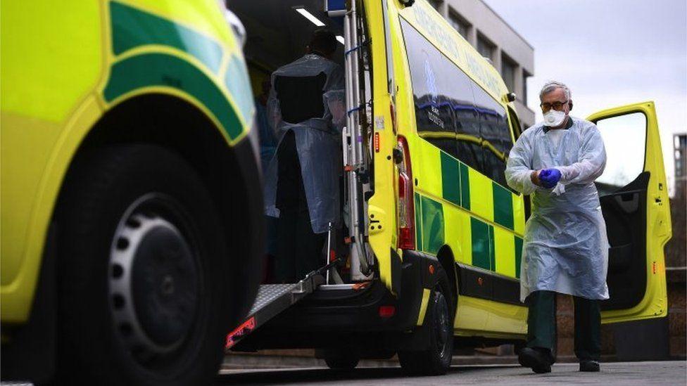 A man in PPE outside an ambulance in London