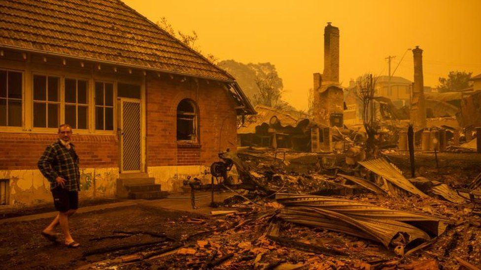 A man stands in front of burnt-out buildings in Cobargo, New South Wales, below an orange sky filled with smoke