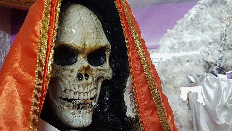 A Santa Muerte statue with cigarettes