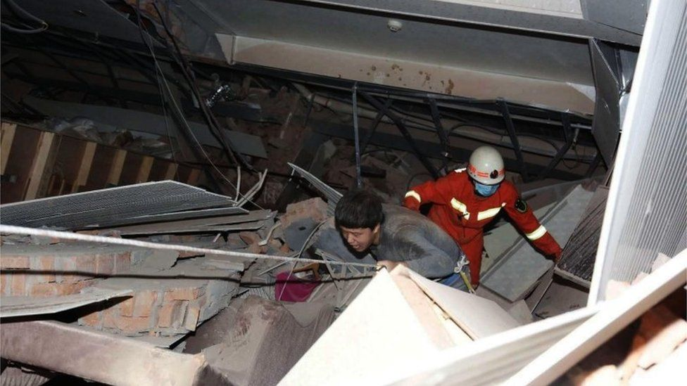 A rescuer follows an injured man walking out of the rubbles of a collapsed five-story hotel building in Quanzhou city in southeast China's Fujian province, 7 March 2020