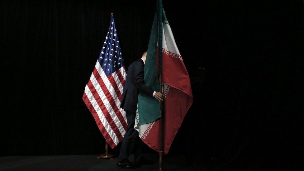 Member of staff removes the Iranian flag from the stage after a group picture with foreign ministers and representatives of Unites States, Iran, China, Russia, Britain, Germany, France and the European Union during the Iran nuclear talks at Austria International Centre in Vienna, Austria on 14 July 2015.