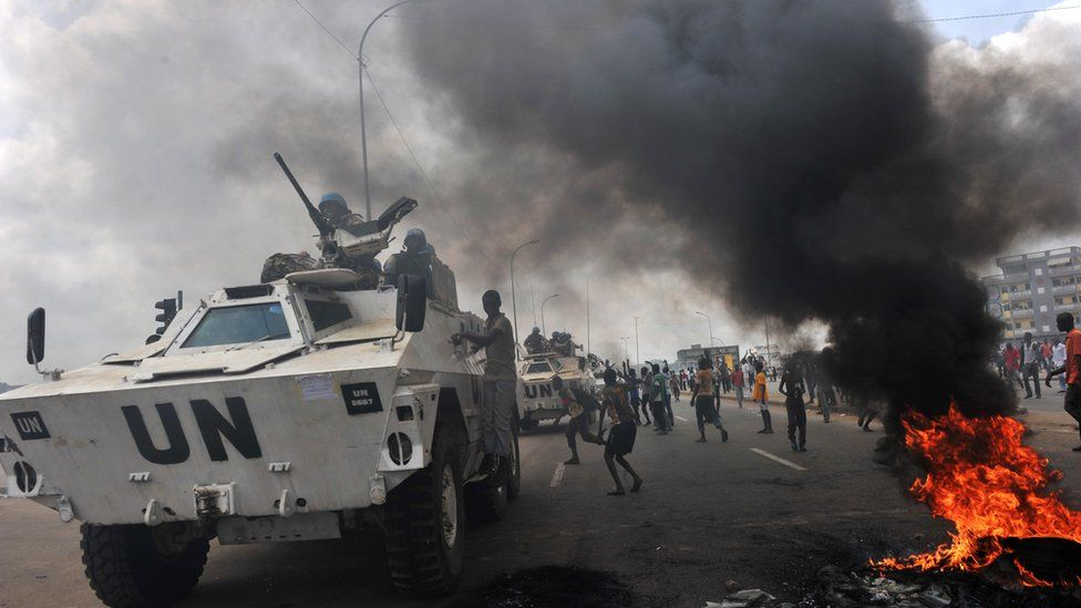A UN tank rolls back by burning tires in a street in Ivory Coast