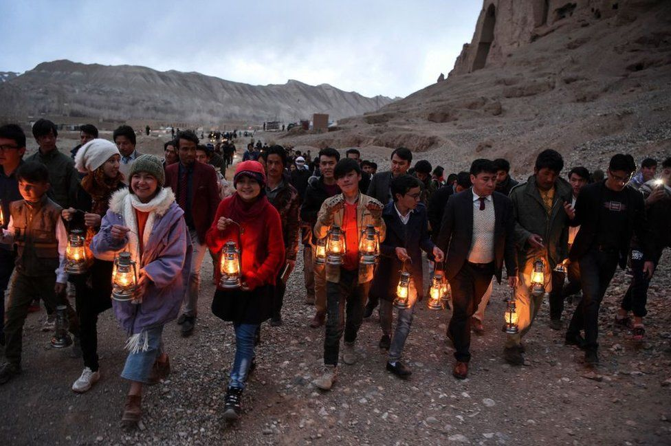Residents and civil society activists hold lamps as they walk to the site where the Salsal Buddha statue once stood