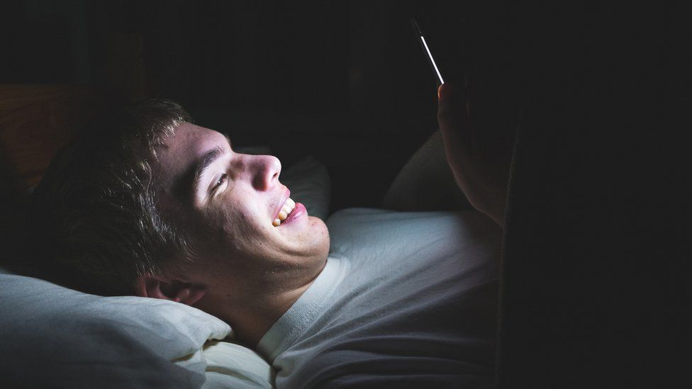 Teenage boy looking at his phone in the dark in bed