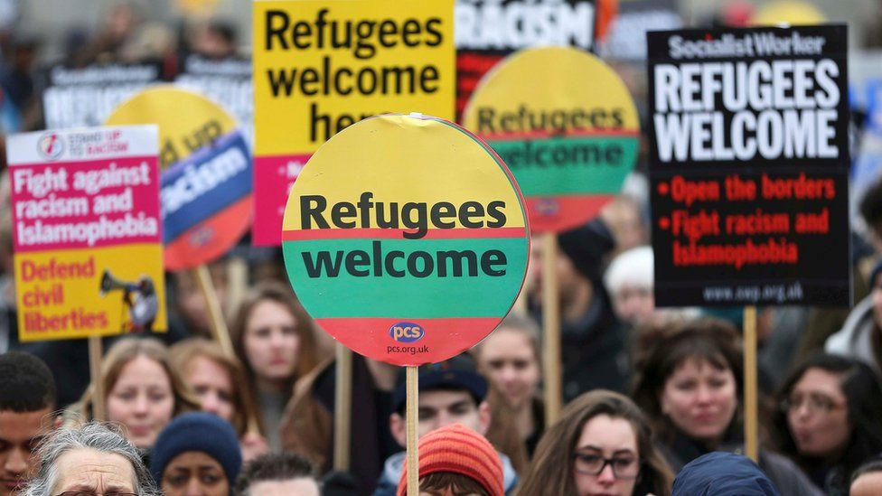 Demonstrators hold placards during a refugees welcome march in London