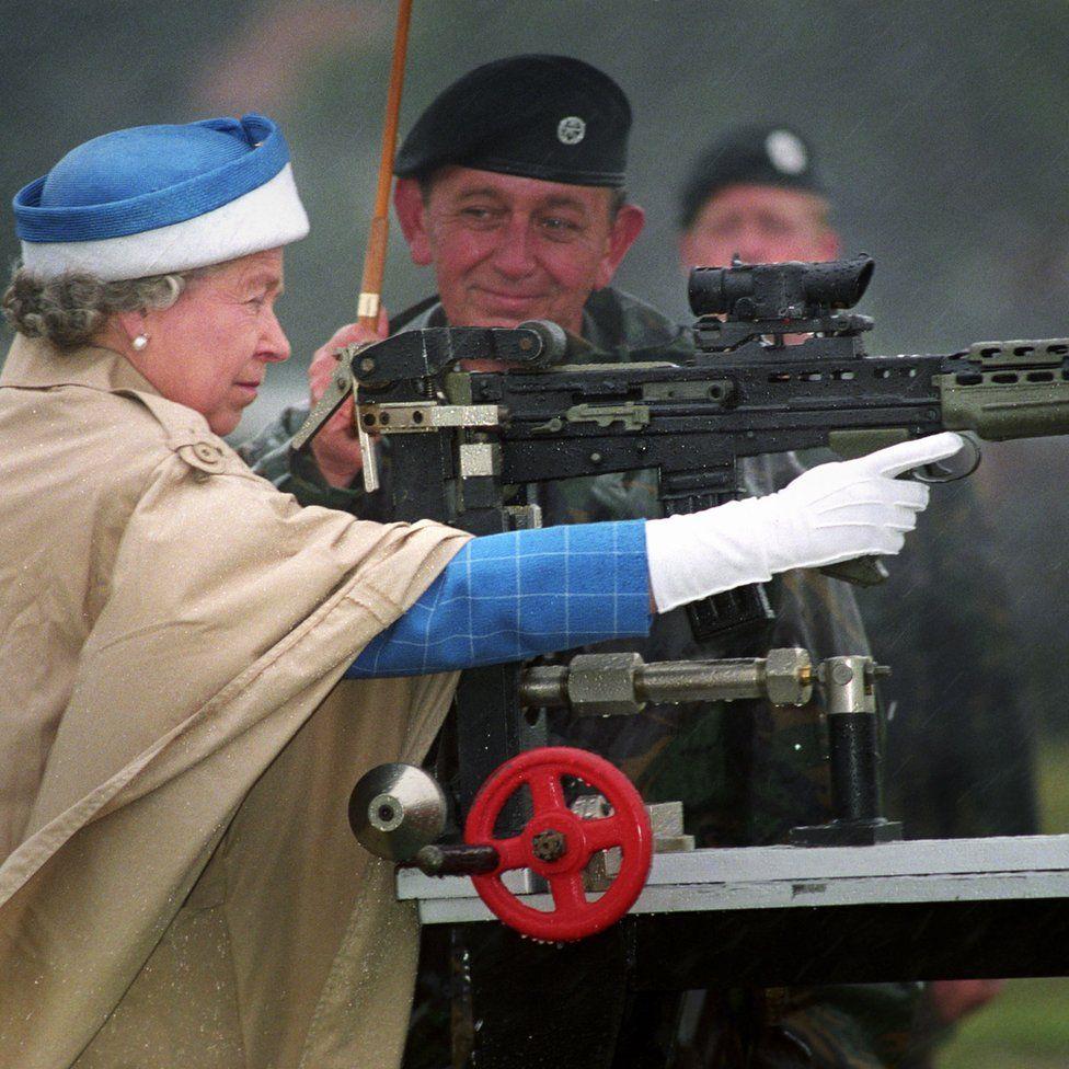 Queen Elizabeth II, with Chief Instructor, firing a standard SA 80 rifle