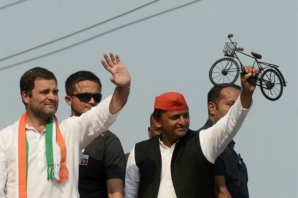 Uttar Pradesh Chief Minister and Samajwadi Party leader Akhilesh Yadav (R) and Congress Vice President Rahul Gandhi (L) wave to the crowd during a joint roadshow in support of their state assembly election party candidates in Varanasi on March 4, 2017.