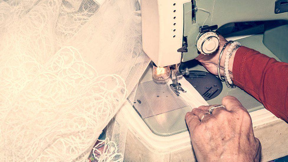 Woman sewing a wedding dress