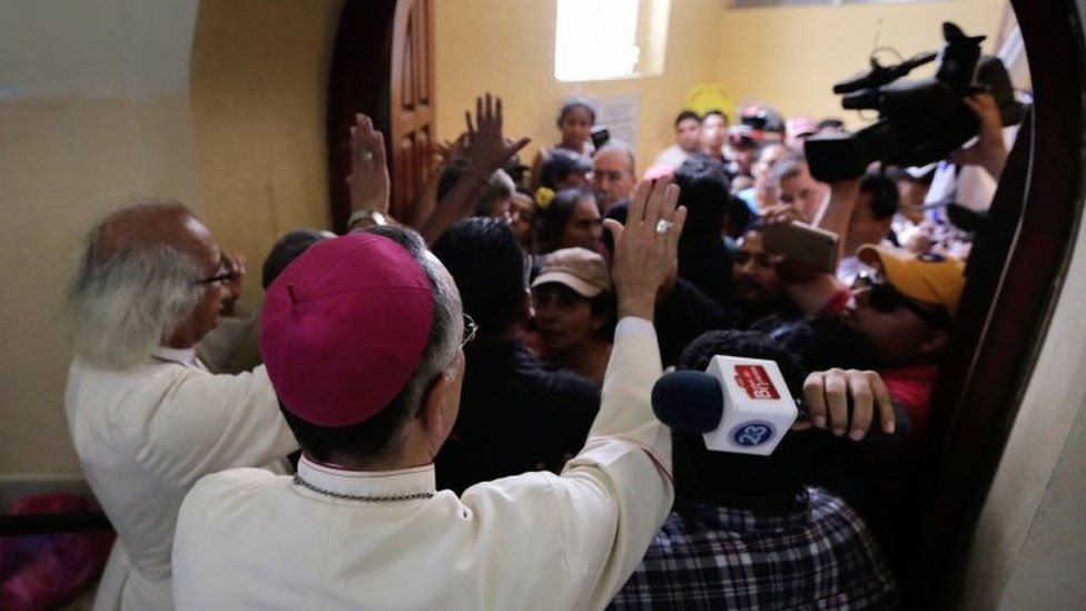 Cardinal Leopoldo Brenes (L) and bishop Silvio Baez try to calm members of the pro-government Sandinista youth down, after arriving at the San Sebastian Basilica in Diriamba, Nicaragua, on July 9, 2018
